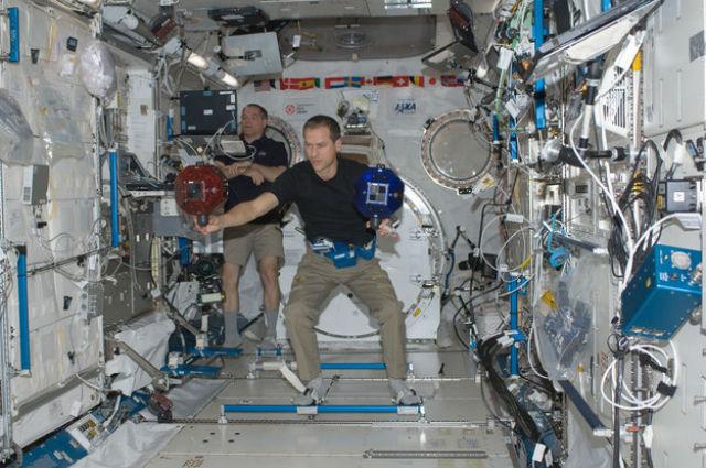 Астронавты Кевин Форд (на заднем плане) и Томас  Маршбёрн располагают двух сферических роботов внутри японского экспериментального модуля Кибо на МКС (фото NASA).