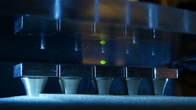 Капля жидкости, застрявшая в узловой точке между генерирующей звук платформой (снизу) и отражающей звук поверхностью (сверху)