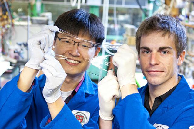 Ведущие авторы разработки Цзеон-Юнь Сунь и Кристофер Кеплингер держат в руках гибкий прозрачный дисплей (фото Eliza Grinnell/SEAS Communications).