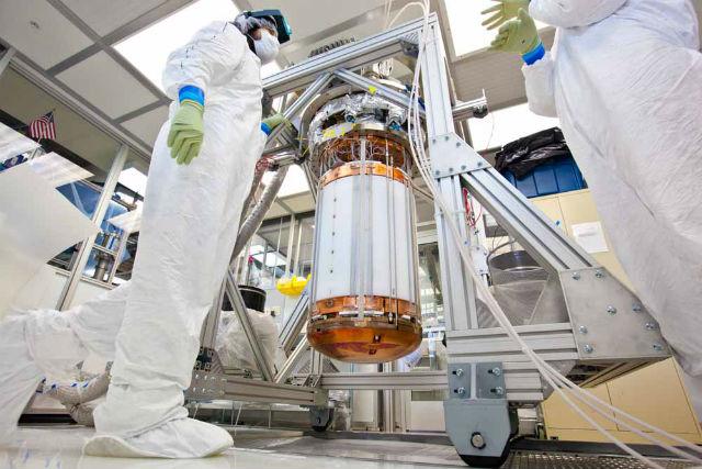 Сотрудники проекта LUX работают с внутренней частью детектора в стерильной комнате, прежде чем поместить прибор в титановый криостат (фото Matt Kapust, Sanford Underground Research Facility).