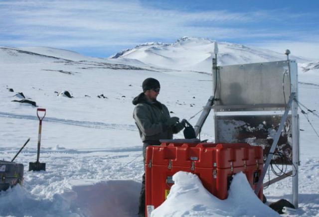 Инженер-полярник настраивает сейсмологическую станцию для проведения исследования (фото Jeremy Miner).